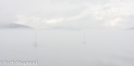Two sailboats iin the mist in Puget Sound
